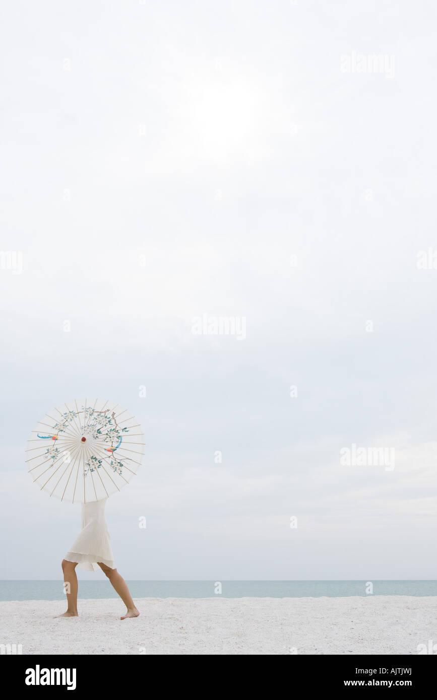 Frau am Strand, Oberkörper versteckt durch Sonnenschirm, Ganzkörperansicht, Seitenansicht Stockbild