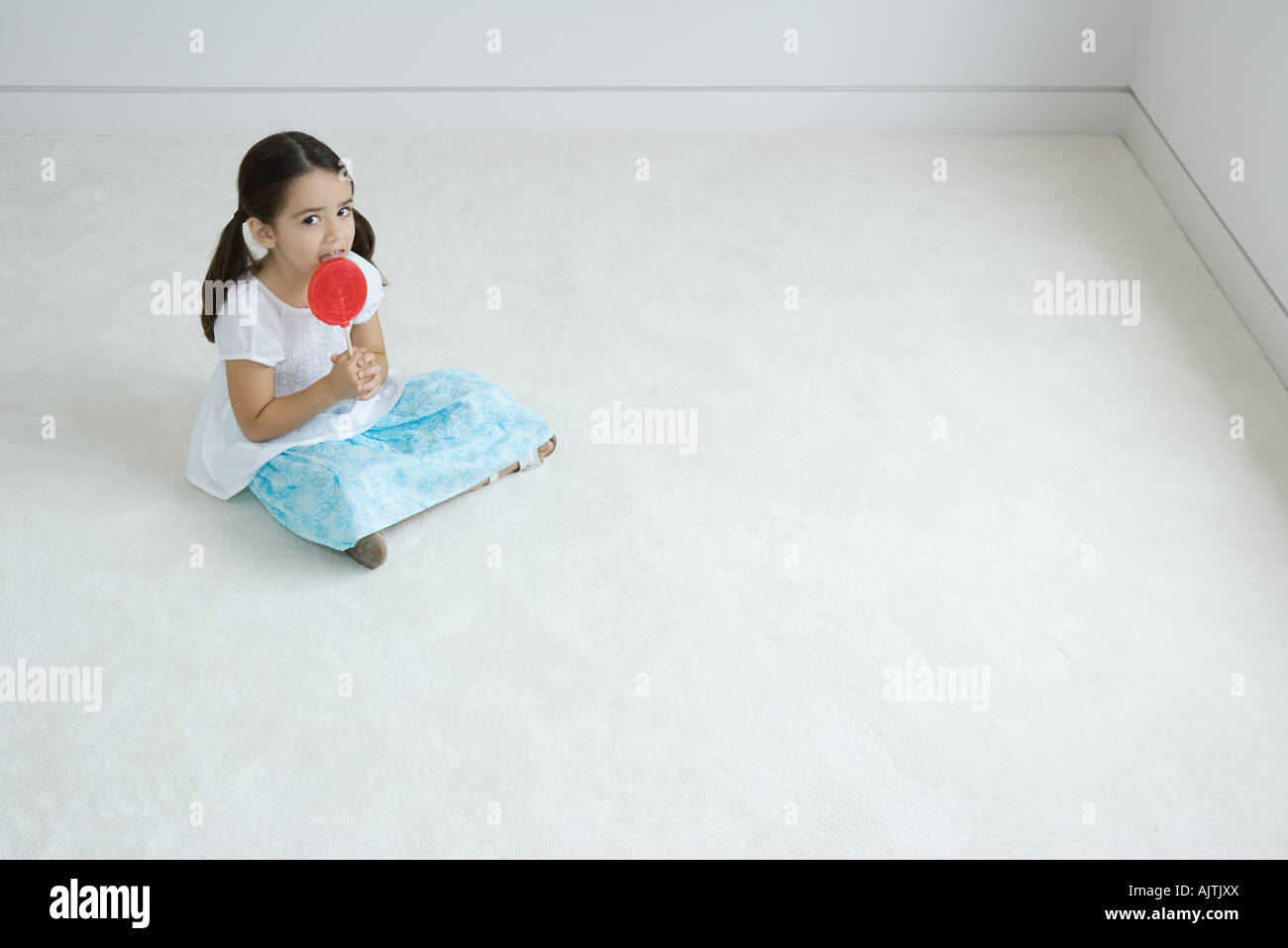 Kleines Mädchen sitzt am Boden, große Lutscher lecken Stockbild