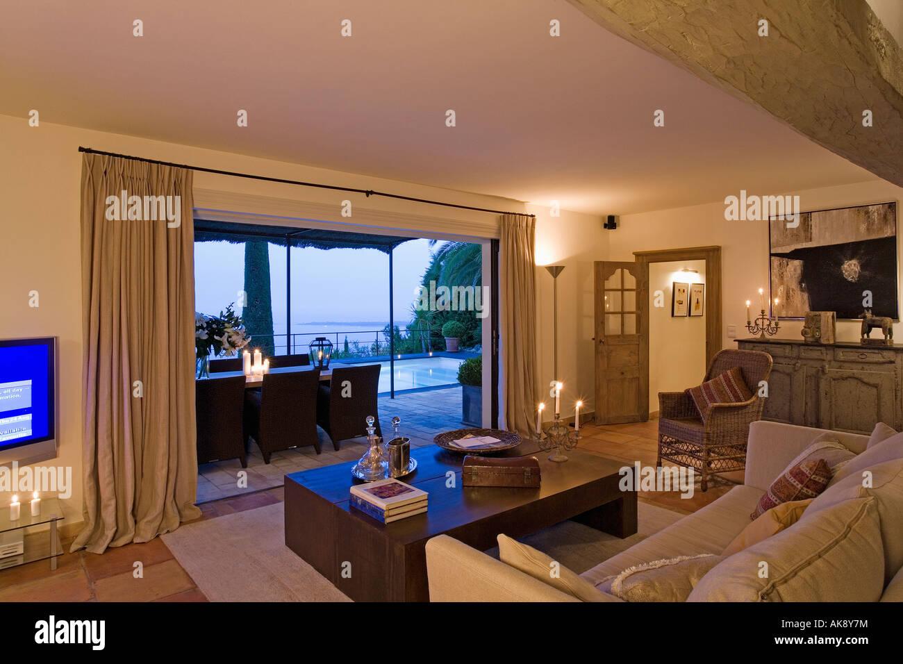 Modernes Wohnzimmer Mit Blick Durch Die Offenen Türen Der Terrasse Am Abend  Stockbild