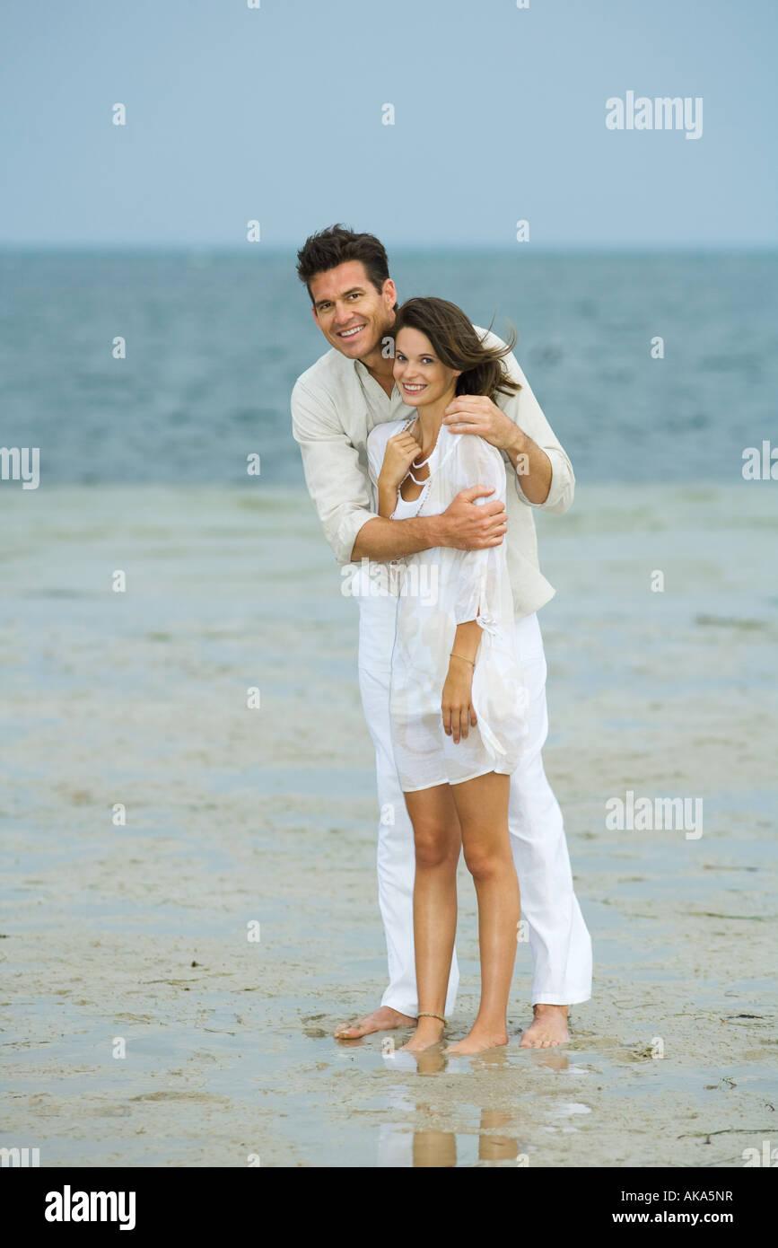 Mann und junge weibliche Begleiter am Strand, zusammenstehen, Blick in die Kamera, in voller Länge Stockbild