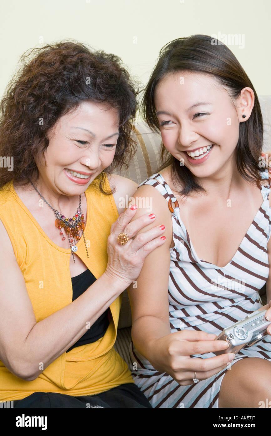 Ältere Frau und ihre Enkelin auf der Suche nach Fotos in einer digitalen Kamera und lächelnd Stockbild