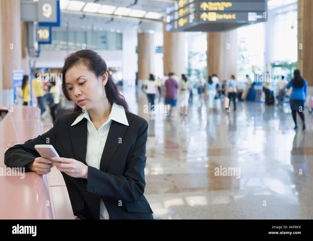 Geschäftsfrau mit einer Hand gehalten Gerät an einem Flughafen Stockbild