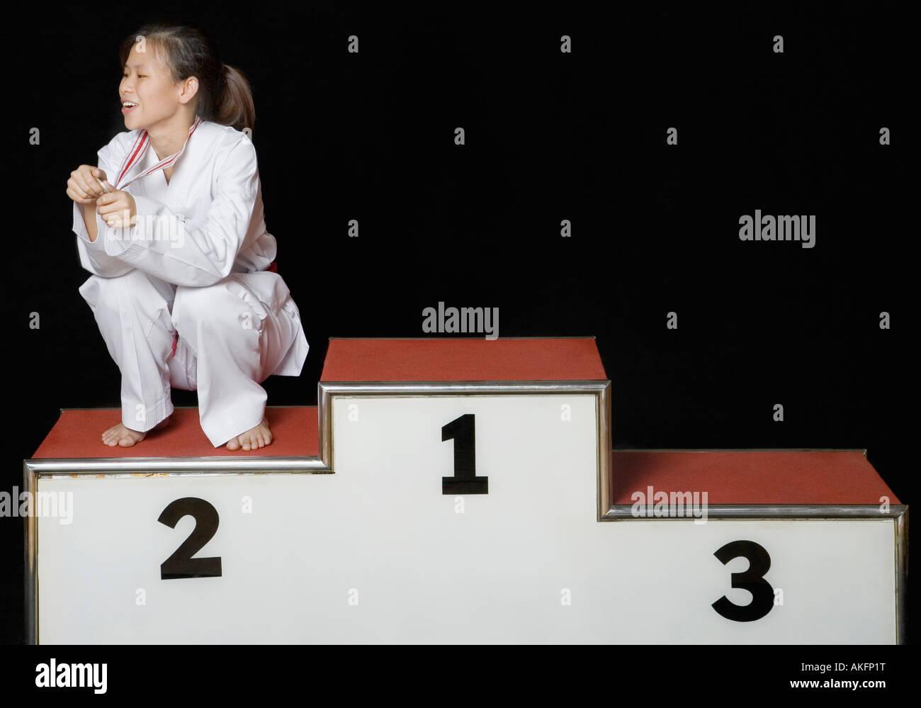 Junge Frau sitzt auf einem Podium Gewinner mit ihrer Medaille Stockbild