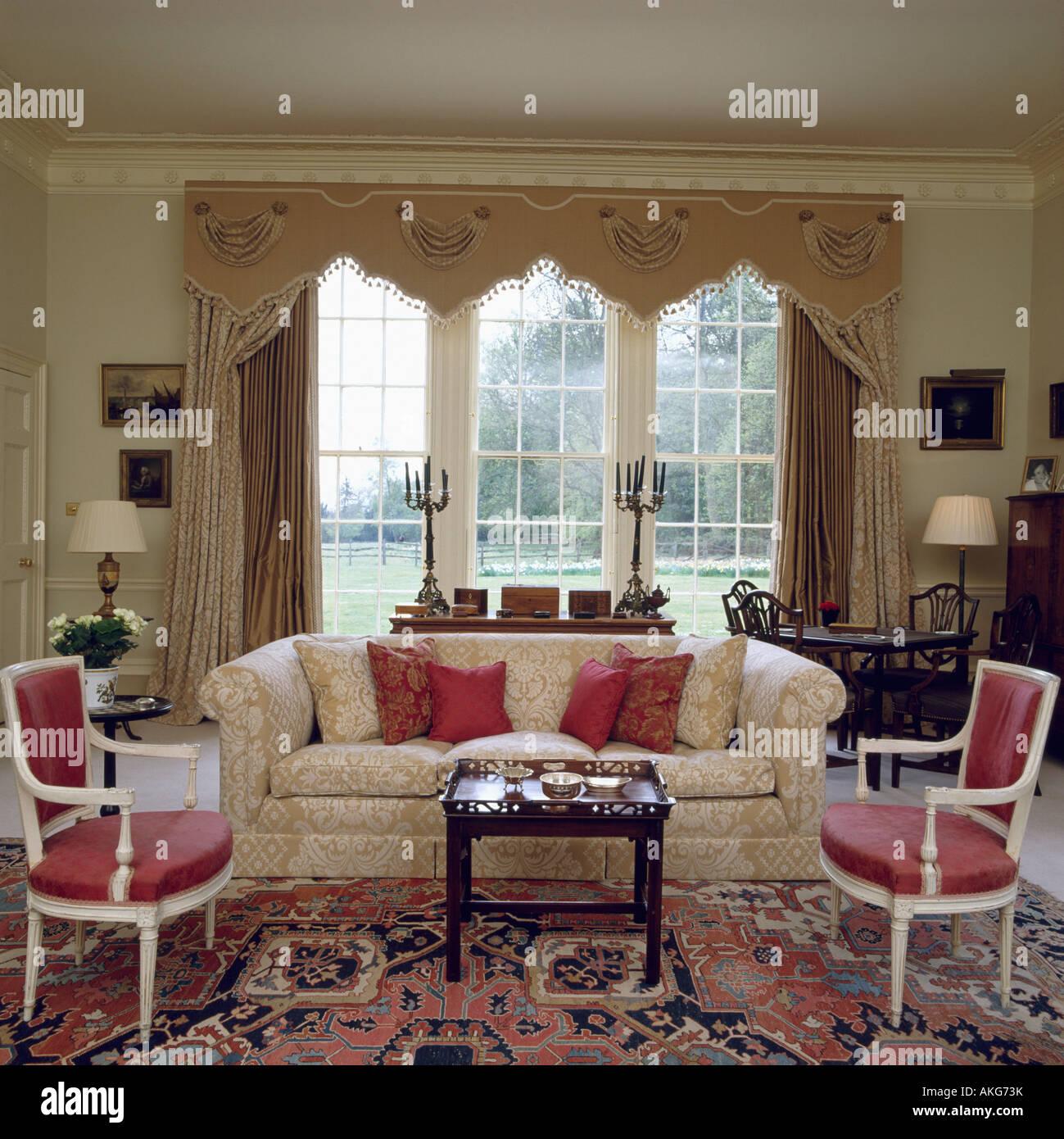 Creme Sofa Vor Fenster Mit Reich Verzierten Profilkranz Und Cremefarbene  Vorhänge Im Traditionellen Landhausstil Wohnzimmer Mit Gemusterten Teppich