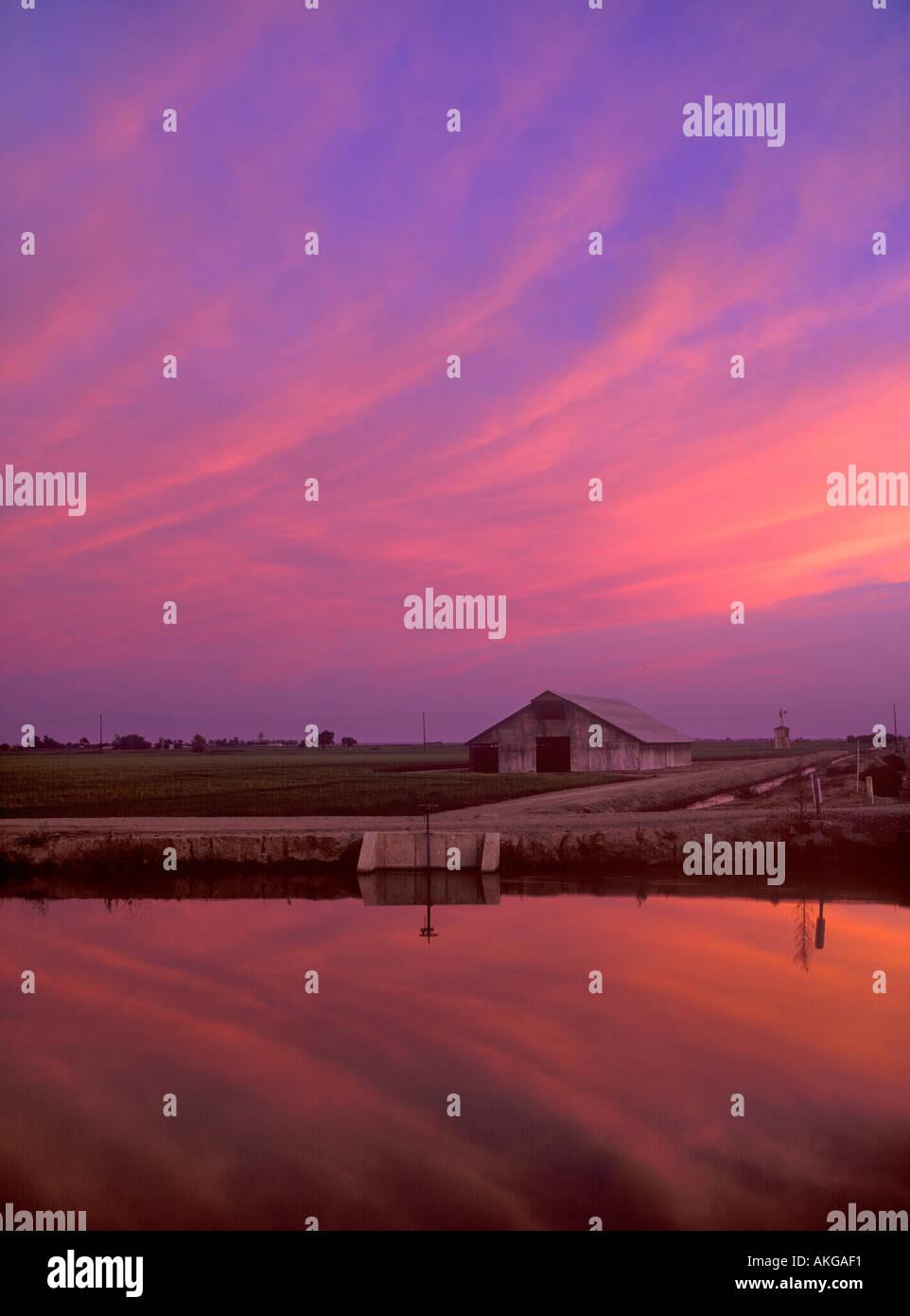 Dramatischen Sonnenuntergang Himmel über einen Bewässerungskanal im Sacramento Valley Kalifornien Stockbild