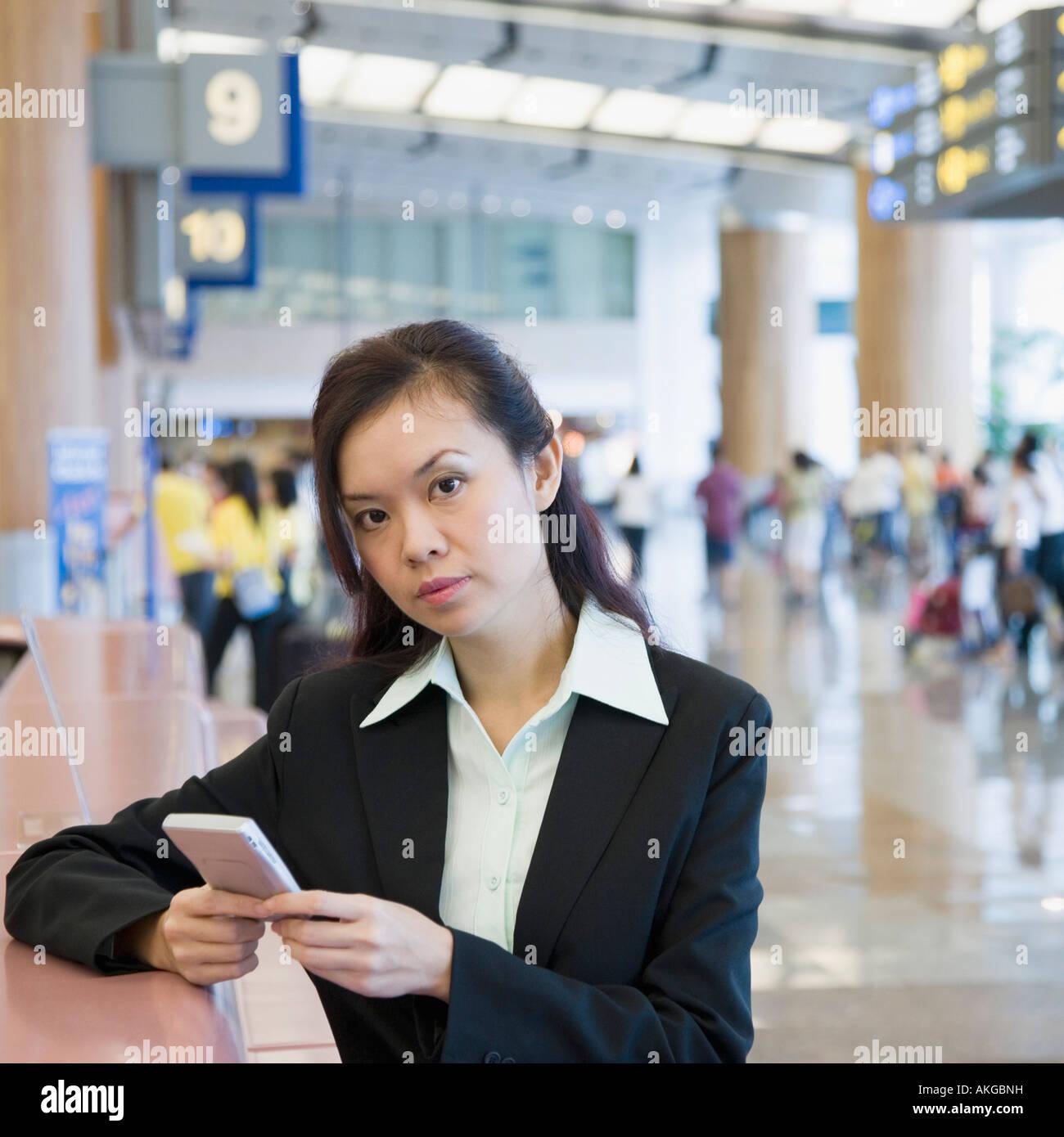Porträt von eine Geschäftsfrau mit einer Hand gehalten Gerät an einem Flughafen Stockbild