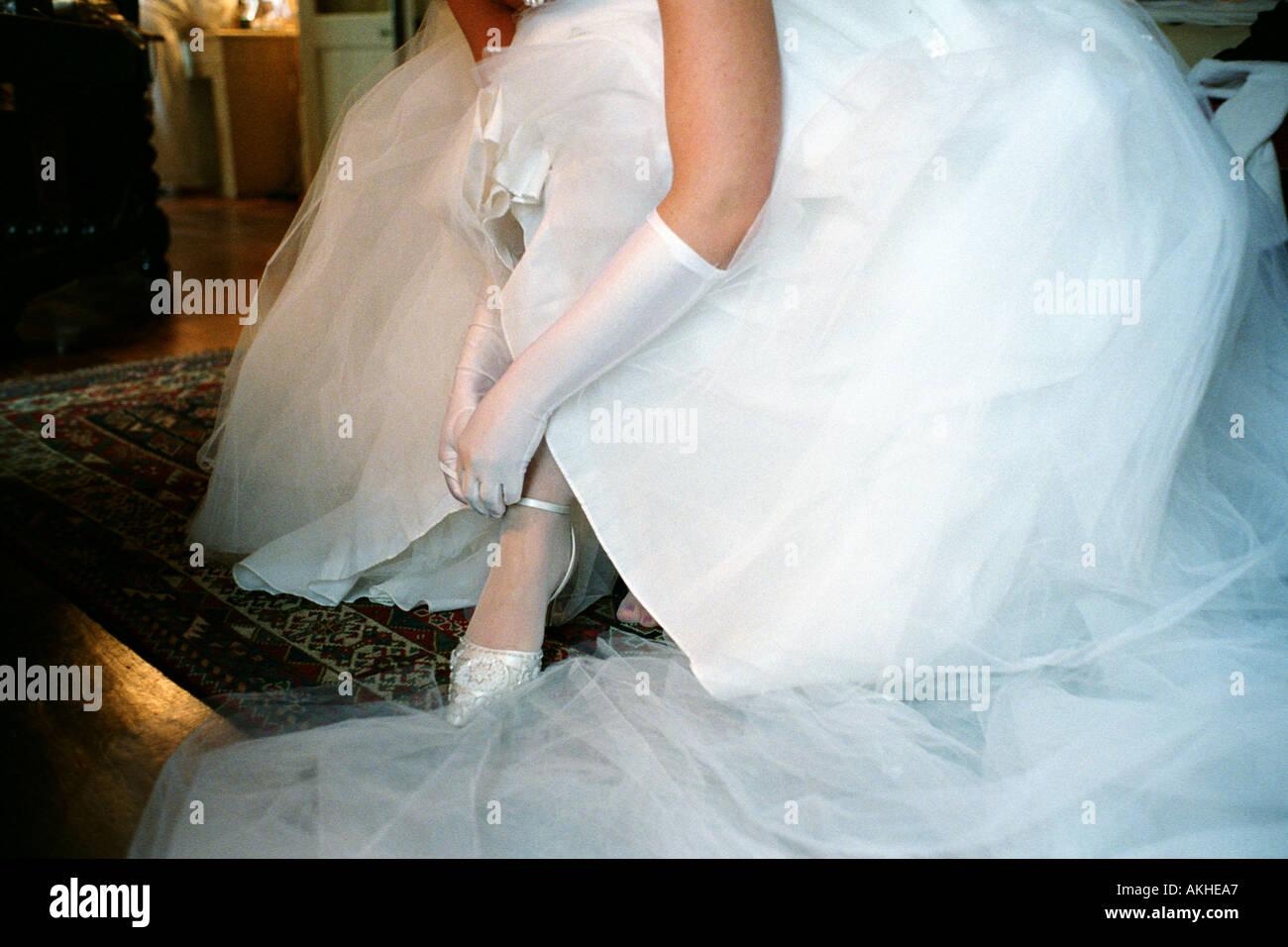 Braut sitzt auf einem Stuhl trägt Hochzeitskleid und ihre Schuhe mit ...