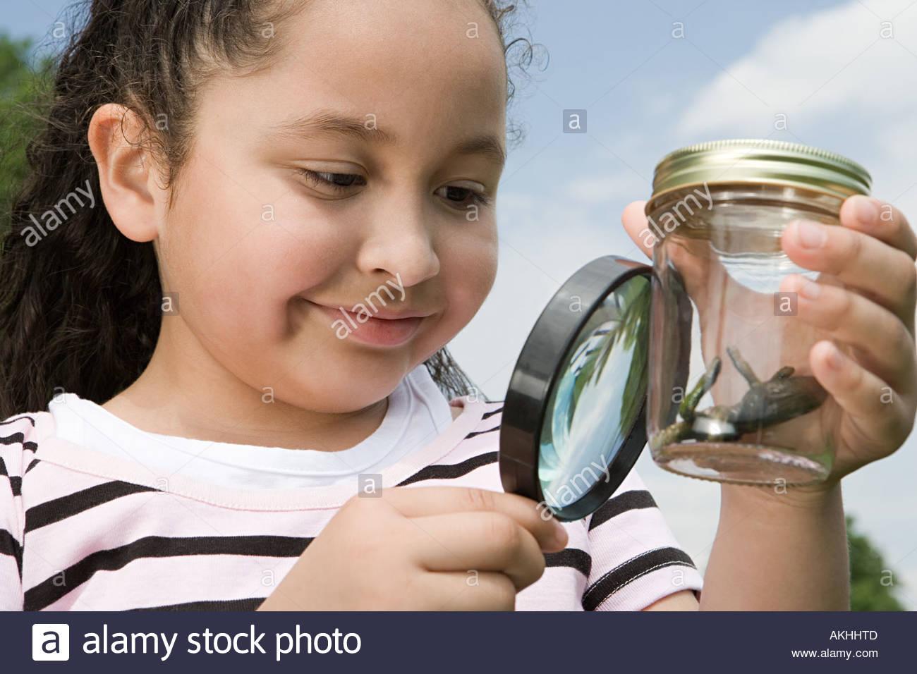 Mädchen betrachten Kreatur in Glas Stockbild