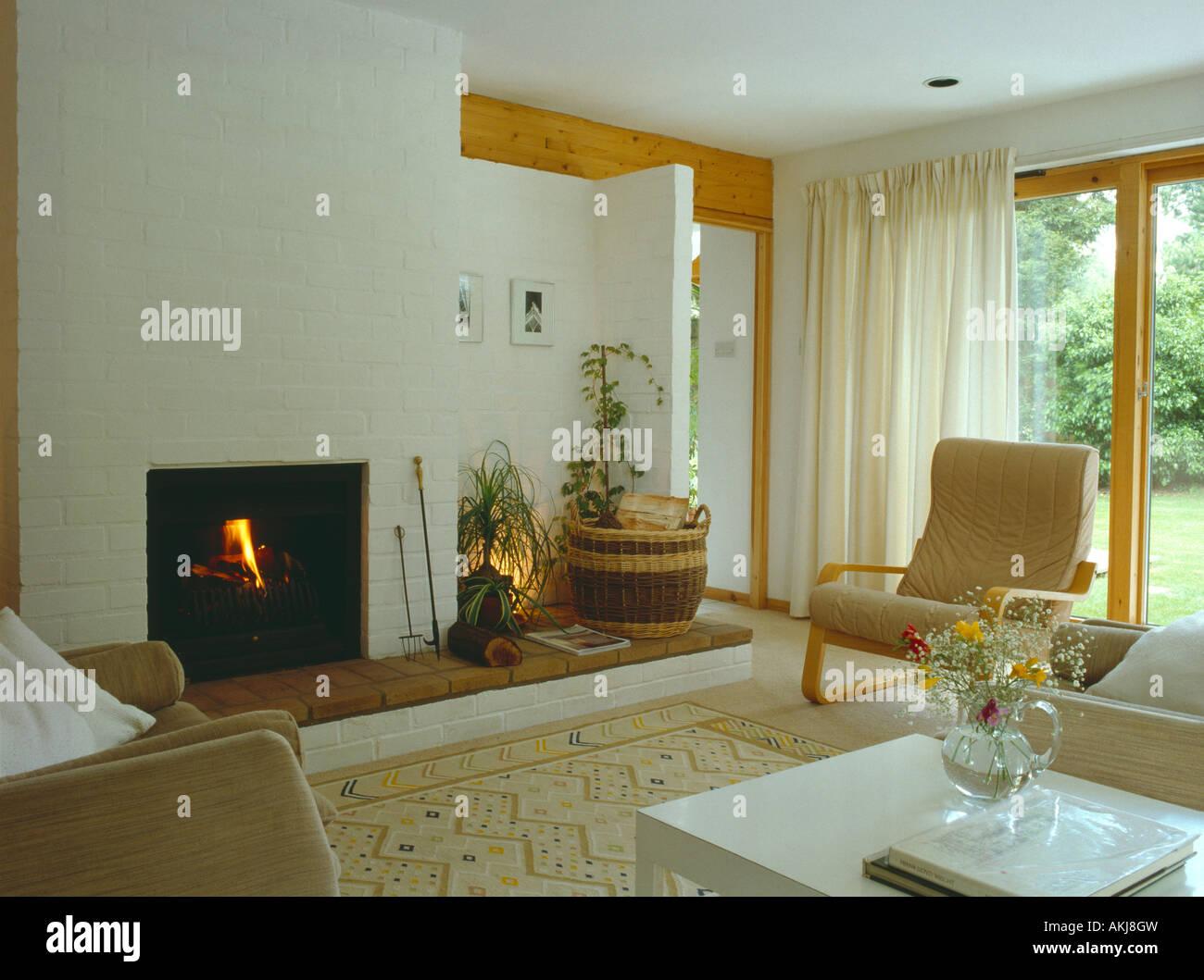 Brennende Feuer und weiße Vorhänge im modernen Wohnzimmer mit ...