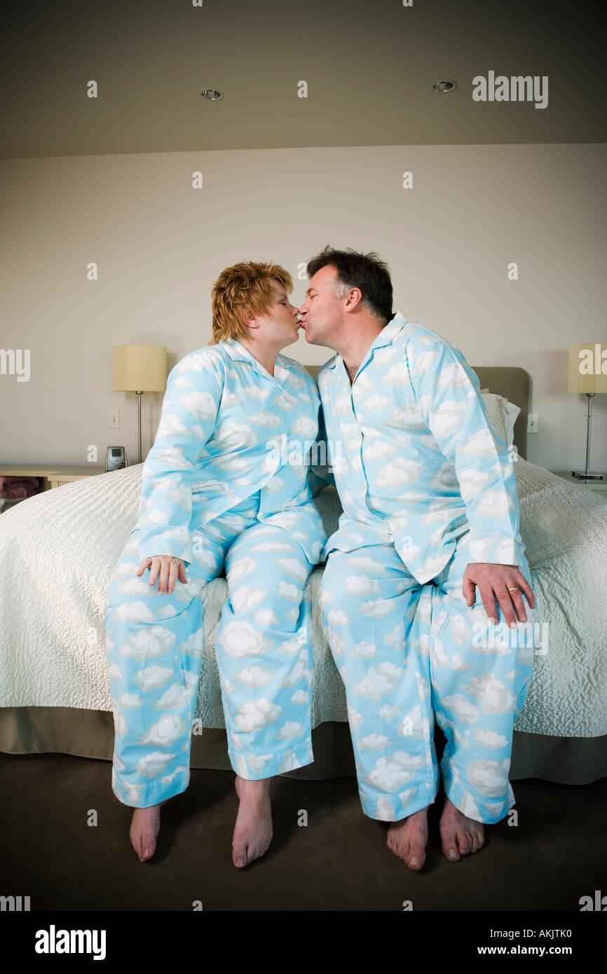 Paar in passenden Pyjamas küssen Stockfoto