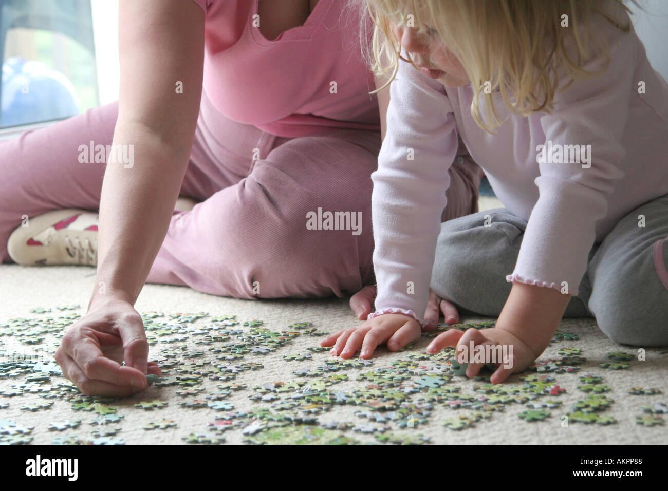 junge Mädchen spielen Puzzle mit Mutter Stockbild