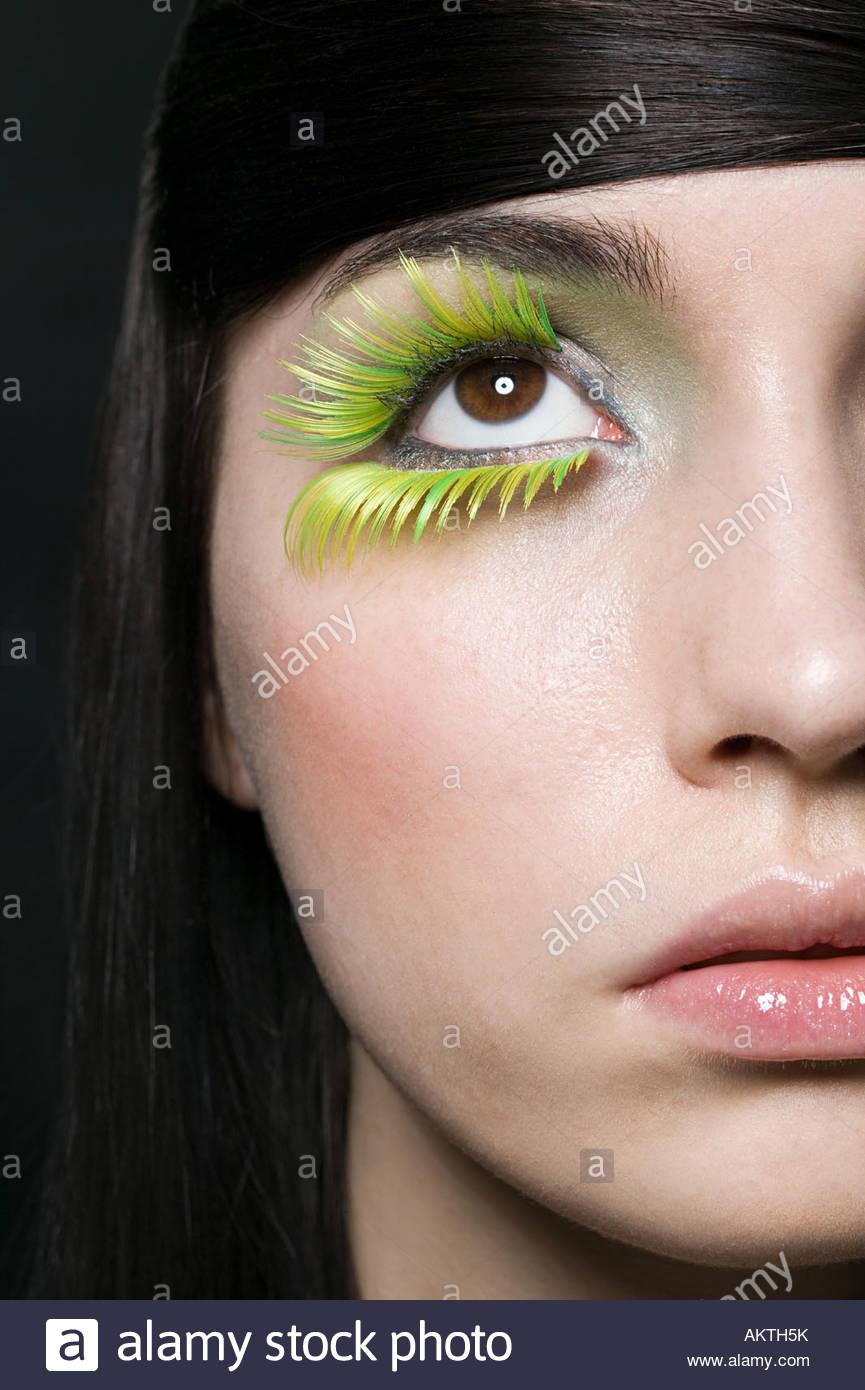 Eine Frau trägt grüne falsche Wimpern Stockbild