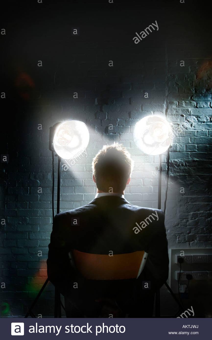 Verhör Szene mit Scheinwerfer leuchten im Gesicht eines Mannes - Rückansicht des zurückhaltenden Stockbild