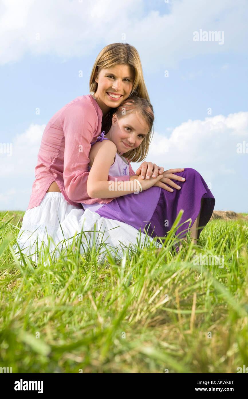 Mutter und Tochter, hockend Stockbild