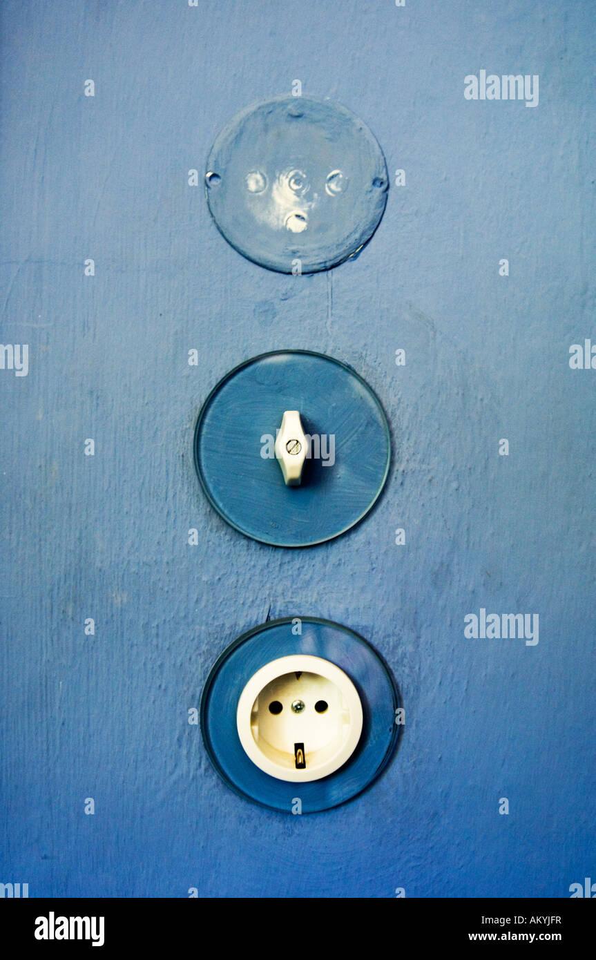 Lichtschalter und Steckdose an der blauen Wand in das Haus des ...