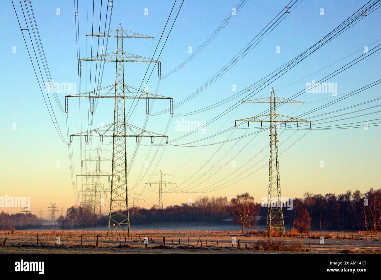 Strommasten - Linien Hochspannung Strom - Sonnenaufgang am Wintermorgen - Schleswig-Holstein, Deutschland, Europa Stockbild