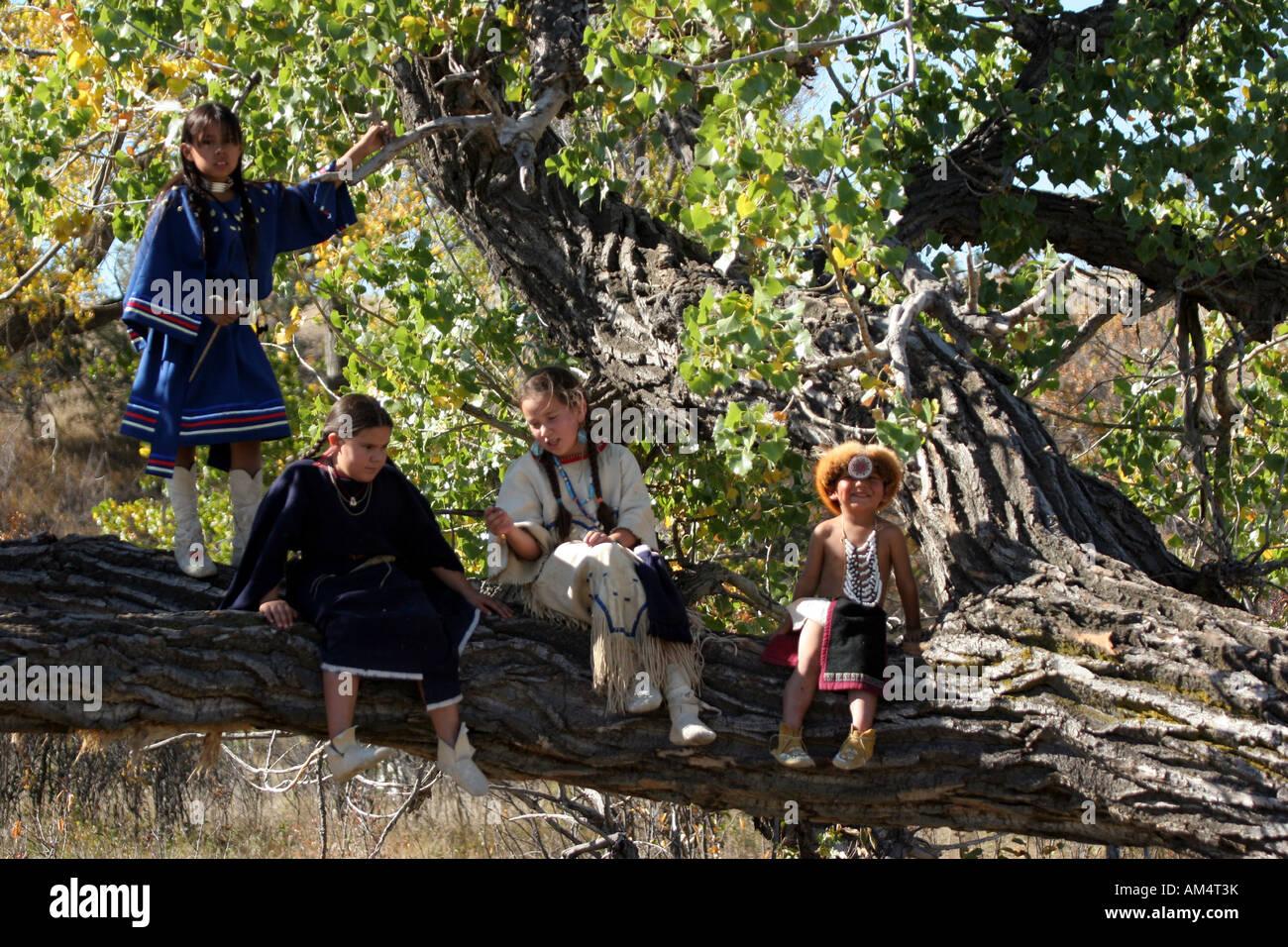 Eine Gruppe von jungen indianischen Kinder spielen in einem alten Baum Stockfoto