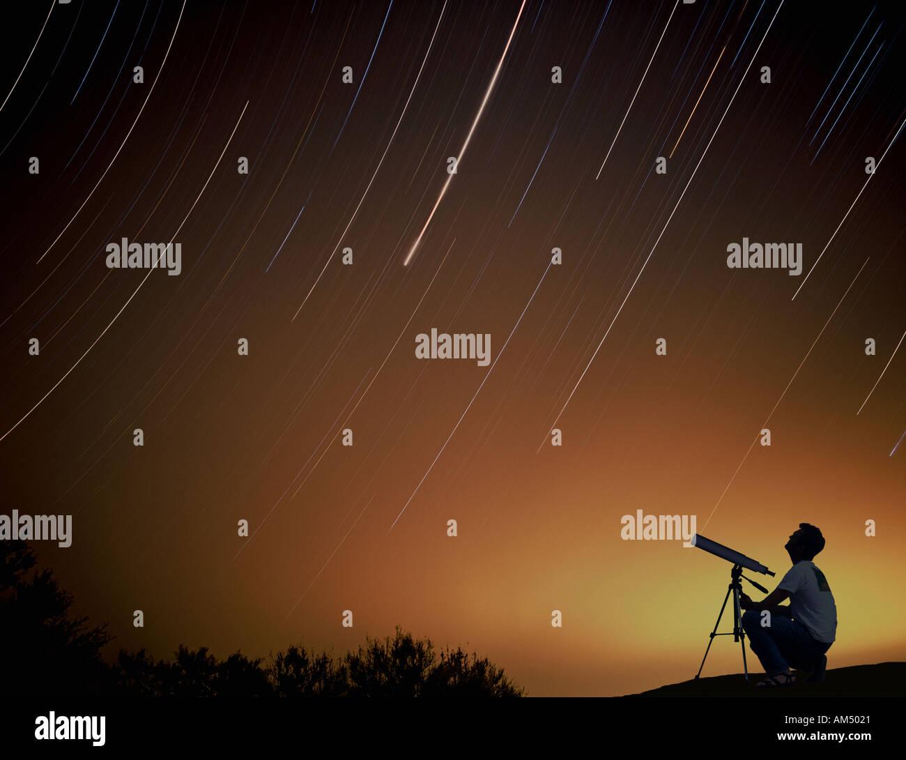 Mann mit Blick auf die Sterne in der Nacht in seinem Hof-Teleskop Stockbild