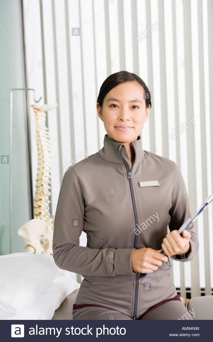 Asiatische weibliche Physiotherapeut mit Diagramm Stockbild