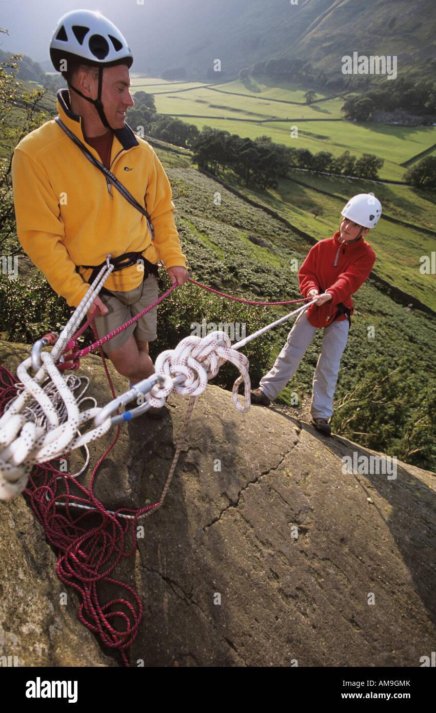 Klettern-Instruktor mit Kind Abseilen im Lake District, Cumbria UK Stockbild
