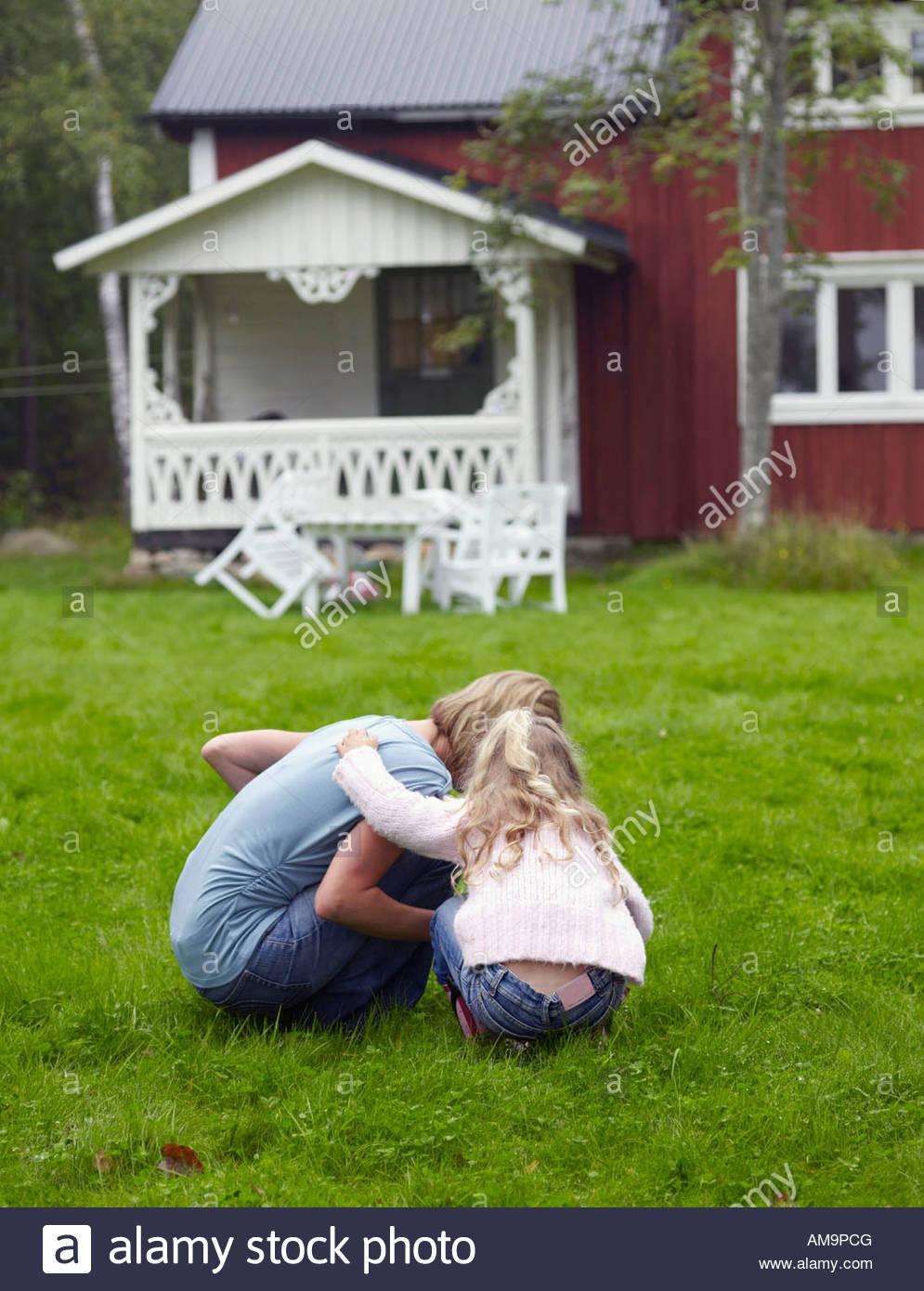 Frau mit jungen Mädchen kauerte in Hof. Stockbild