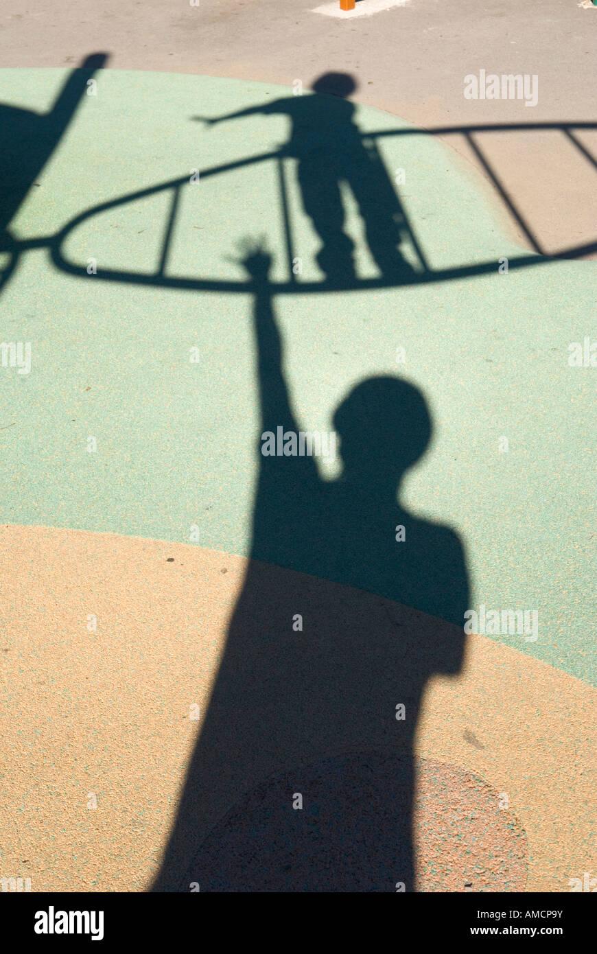 Schatten des kleinen Kindes auf Klettergerüst Schatten des Erwachsenen Spielplatz Stock überragt Stockbild