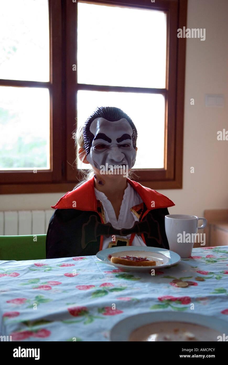 ein junges Mädchen sitzt beim Frühstück im Kostüm mit Dracula Maske und Kostüm Stockbild