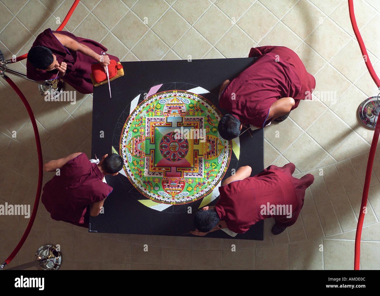 Vier Mönche arbeiten auf eine fast fertige mandala Stockbild