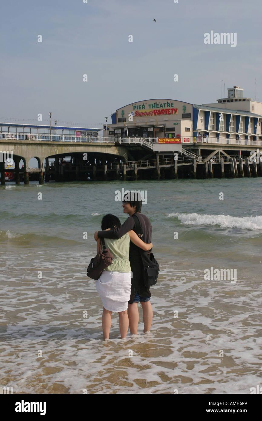 Asiatische fremdsprachige Studierende umarmen am Strand vor Bournemouth Pier, Bournemouth, Dorset, UK. Sept. 2006. Stockfoto