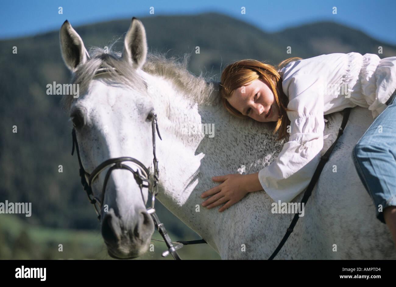 Teenager-Mädchen auf dem Pferd liegend Stockbild