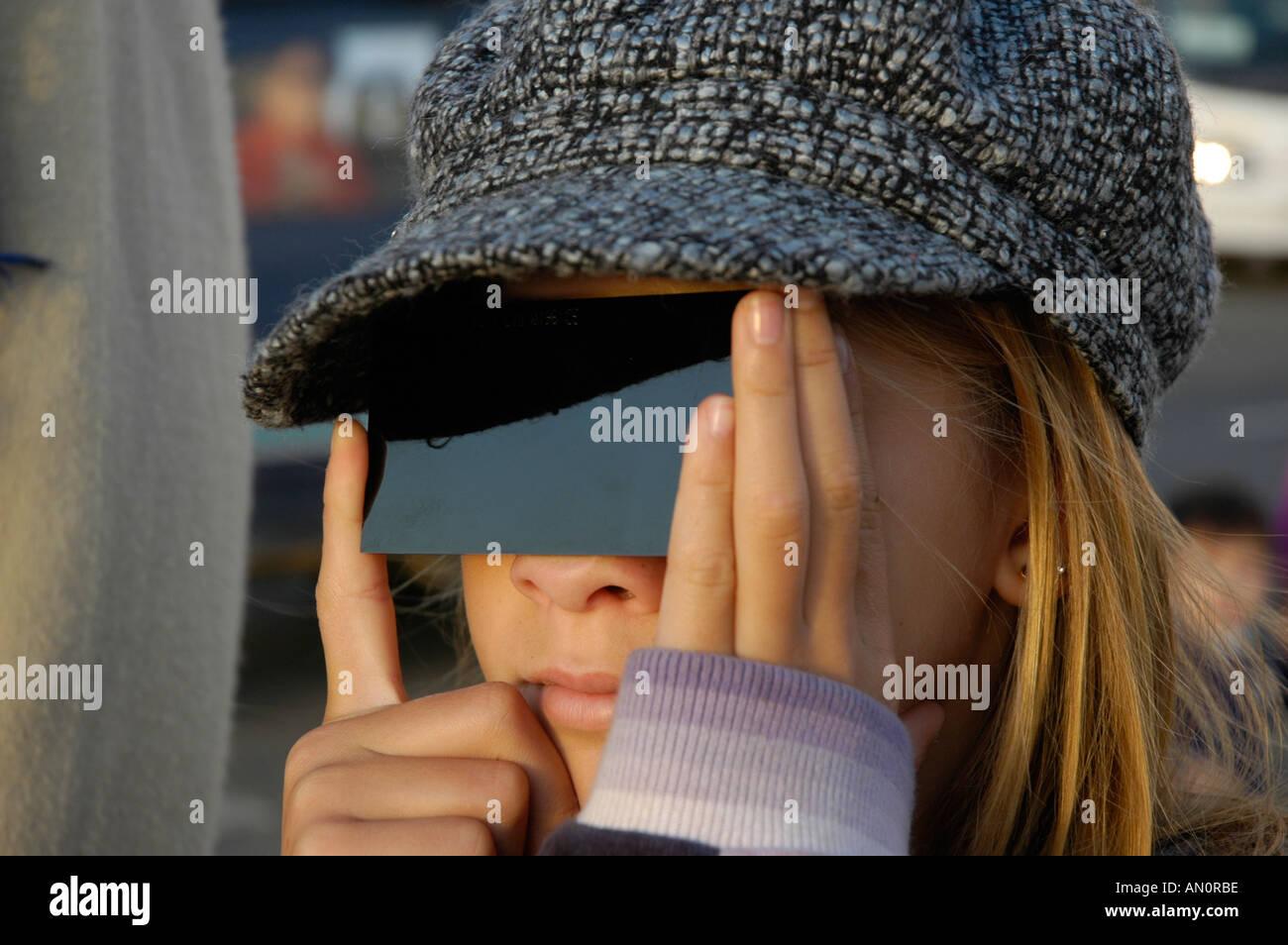 Eine Mädchen schaut eine Sonnenfinsternis durch Schutzglas in Formentera Spanien Stockbild
