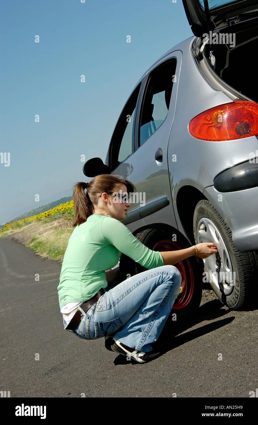 Frau der Radwechsel / Reifen für einen Ersatz Reifen auf ihrem Auto Stockbild