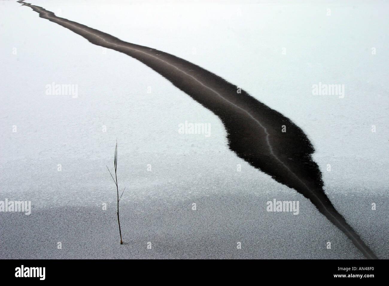 Dunkle schwarze Riss im Schnee bedeckt dünnes Eis Stockbild