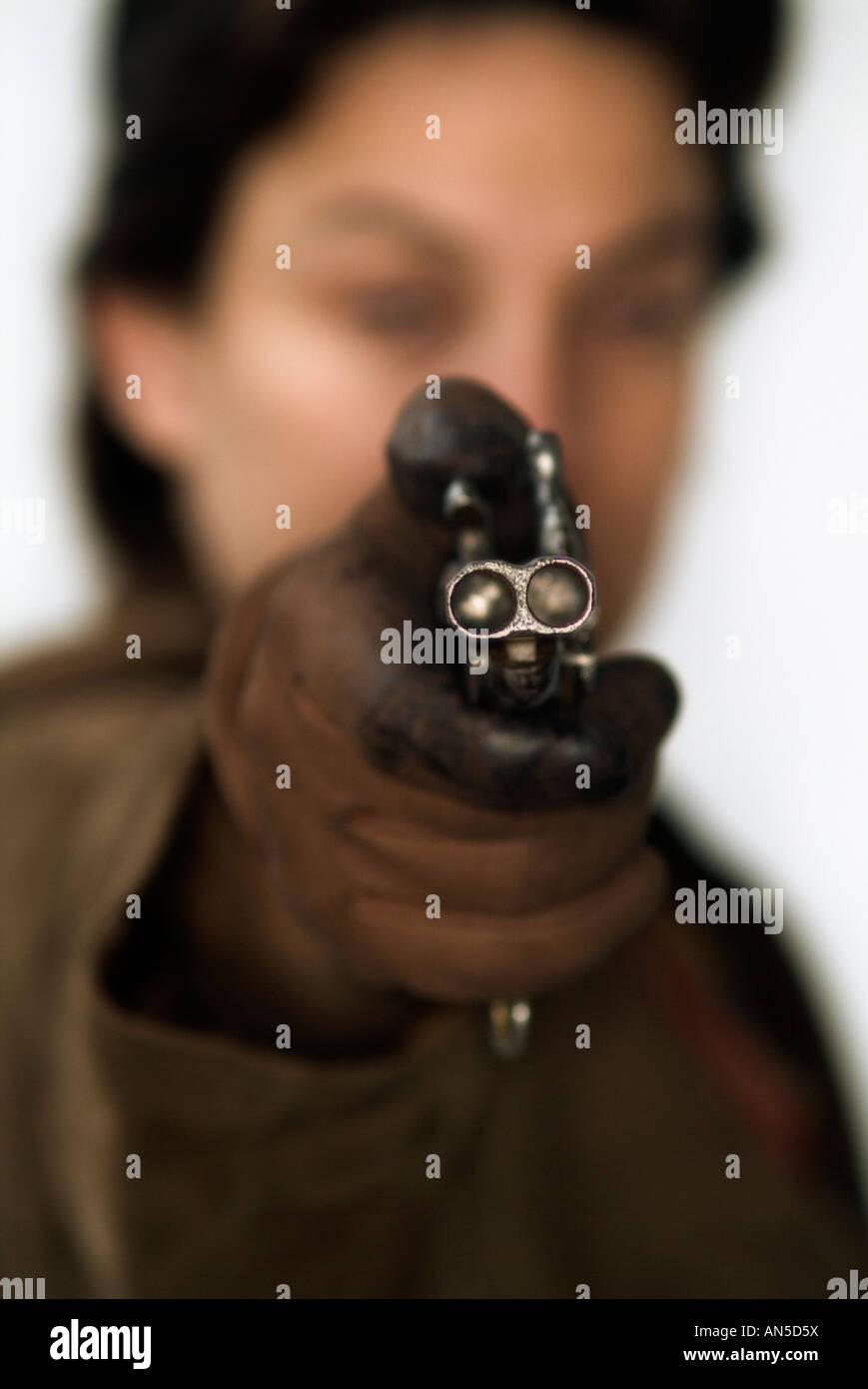 Unerkennbar Person mit dem Ziel, die Kamera mit einer doppelläufigen Pistole Stockfoto