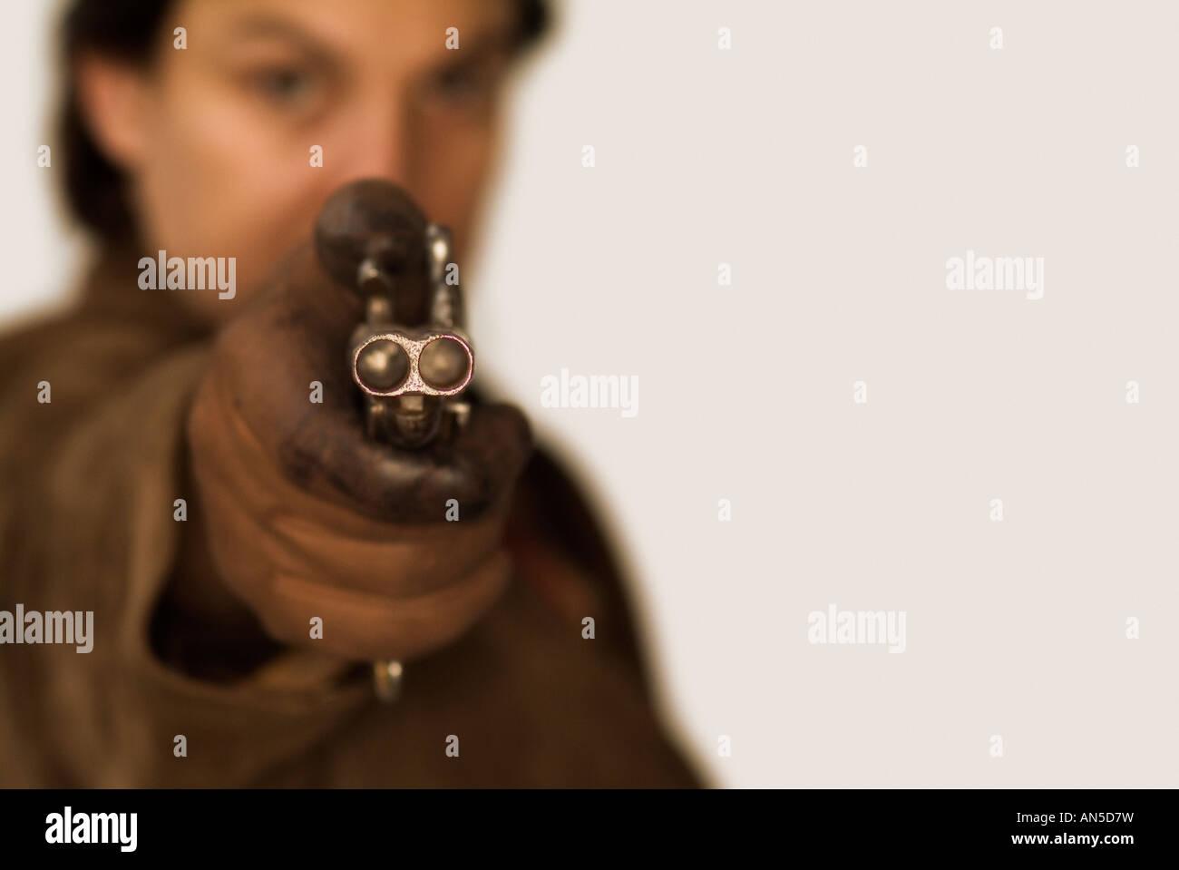 Unerkennbar Person mit dem Ziel, die Kamera mit einer doppelläufigen Pistole Stockbild