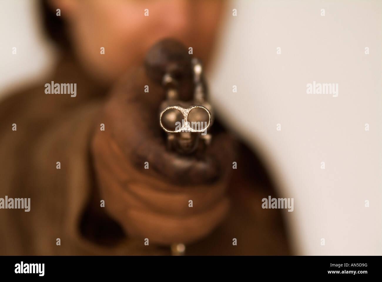 Person mit dem Ziel, die Kamera mit einer doppelläufigen Pistole Stockbild