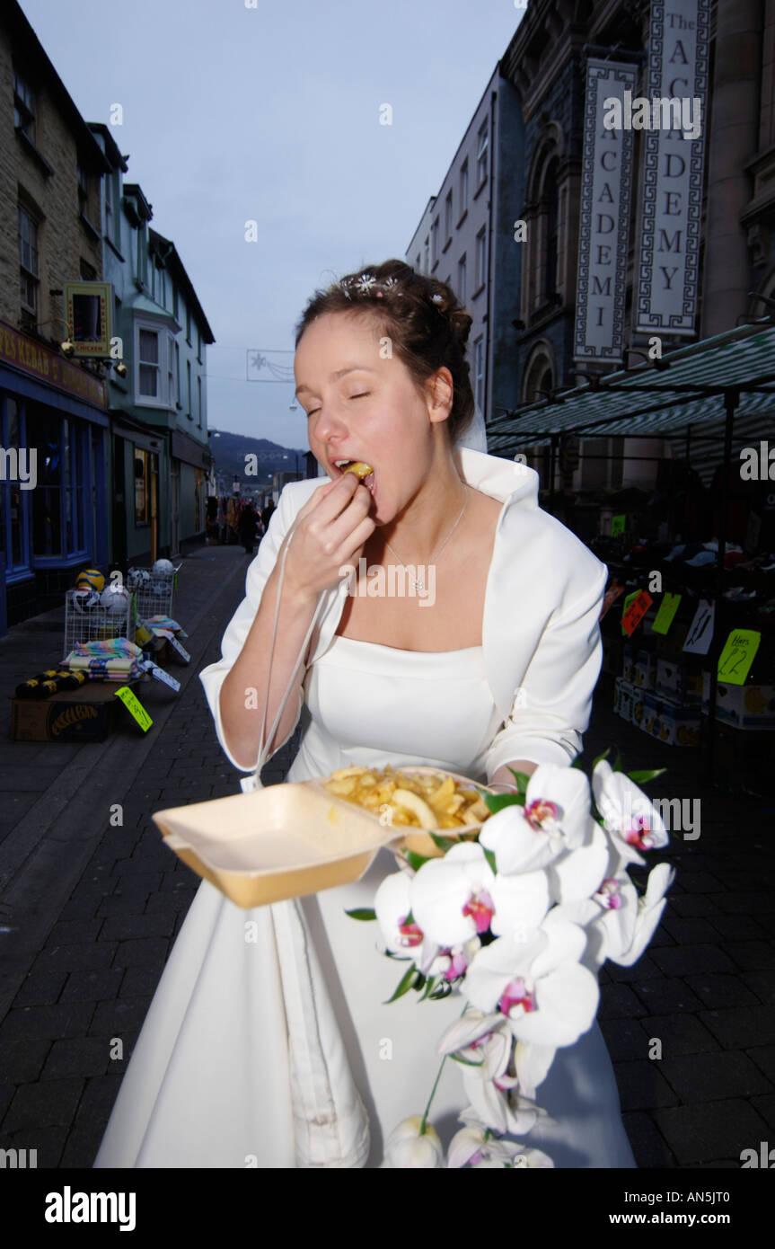 Braut in ihrem weißen Kleid Essen einen Beutel der Späne im Freien ...