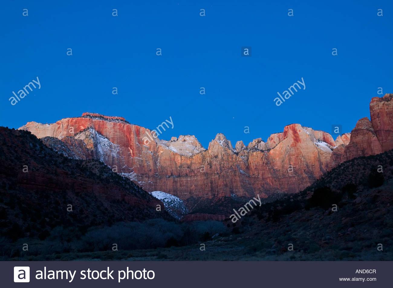 Die Gipfeln, die die Türme der Jungfrau im Zion Nationalpark, Utah umfassen Leuchten von Alpenglühen kurz Stockbild