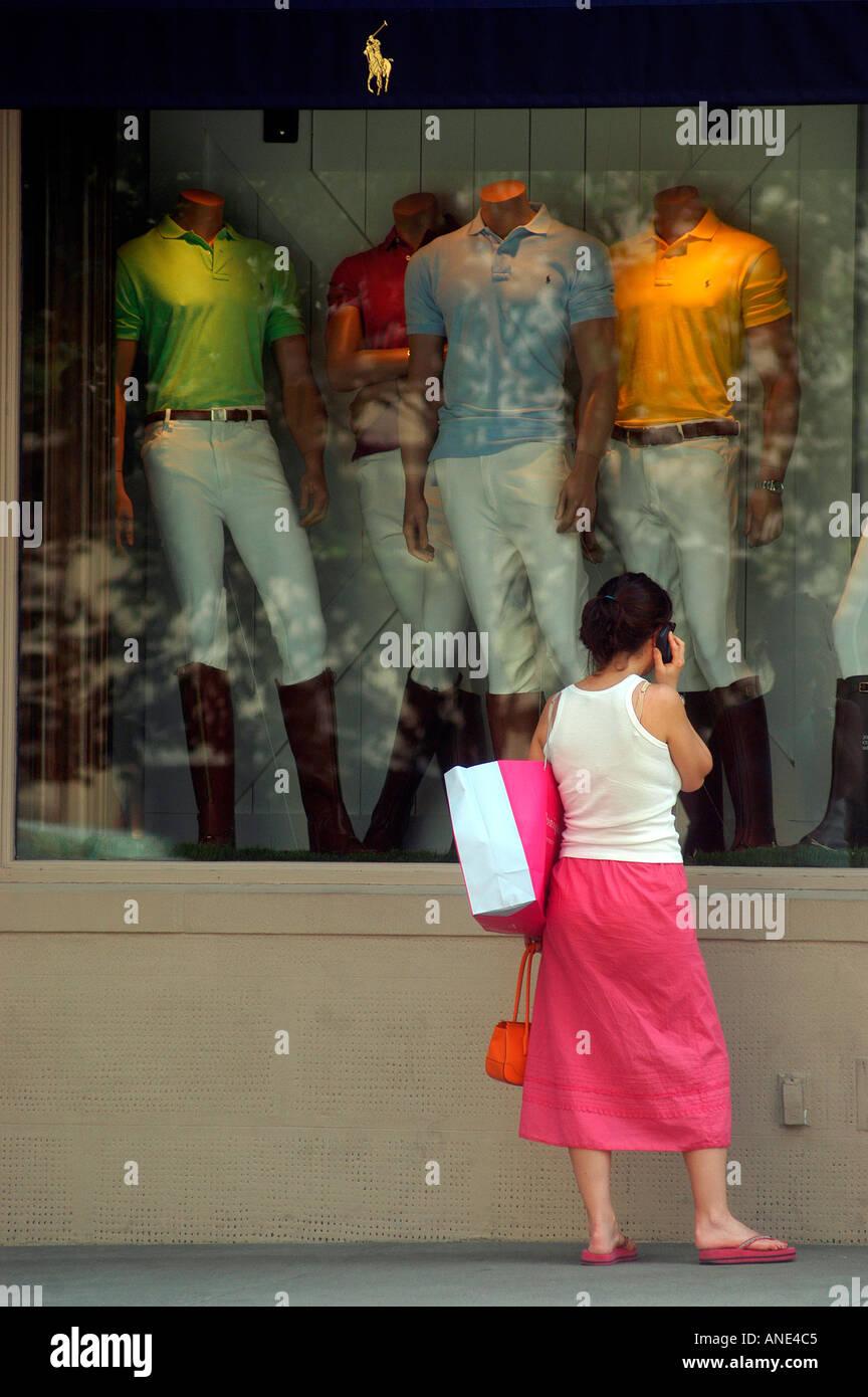 Eine Frau auf ihr Handy in ein rosa und weißes Outfit Fenster Läden auf der  Madison 461b2e2685