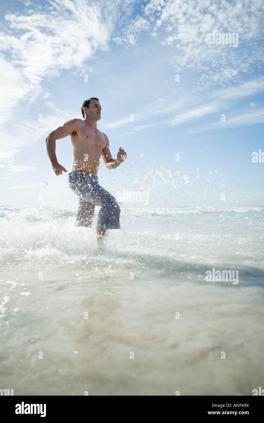 Junger Mann läuft durch Brandung, niedrigen Winkel Ansicht Stockbild