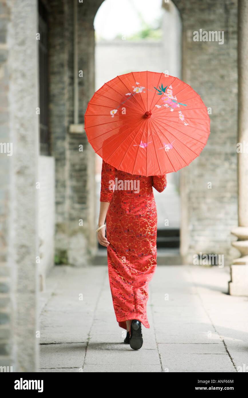 Junge Frau, gekleidet in traditioneller chinesischer Kleidung Wandern mit Sonnenschirm, Rückansicht Stockbild