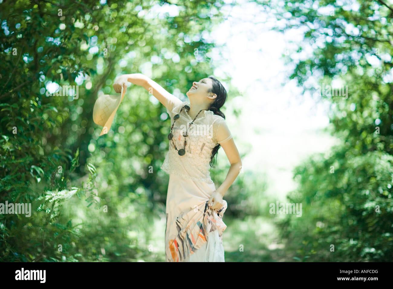 Junge Frau im Wald stehen, werfen sich Sonnenhut Stockbild