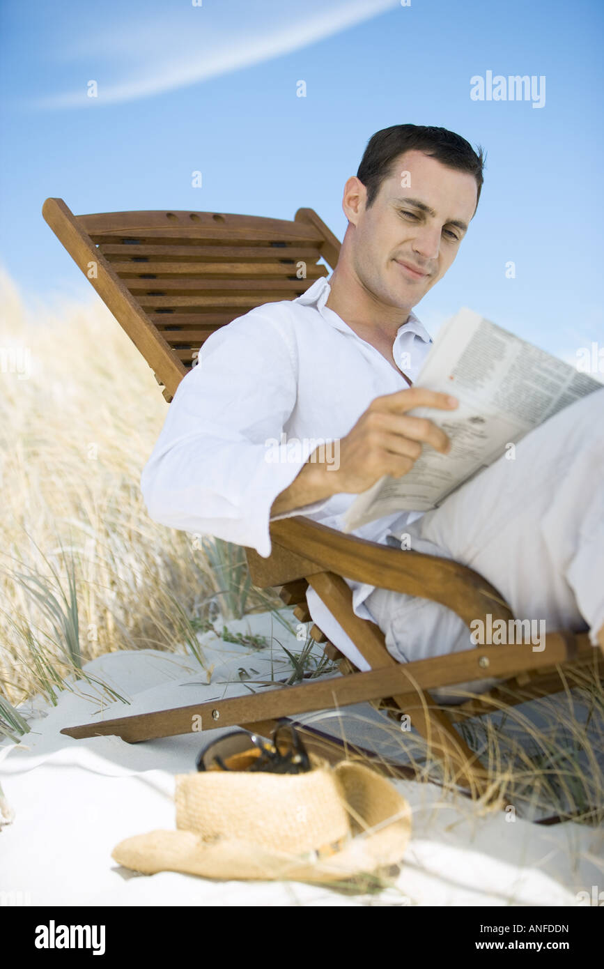 junger mann sitzt im liegestuhl am strand lesen zeitung stockfoto bild 15512048 alamy. Black Bedroom Furniture Sets. Home Design Ideas