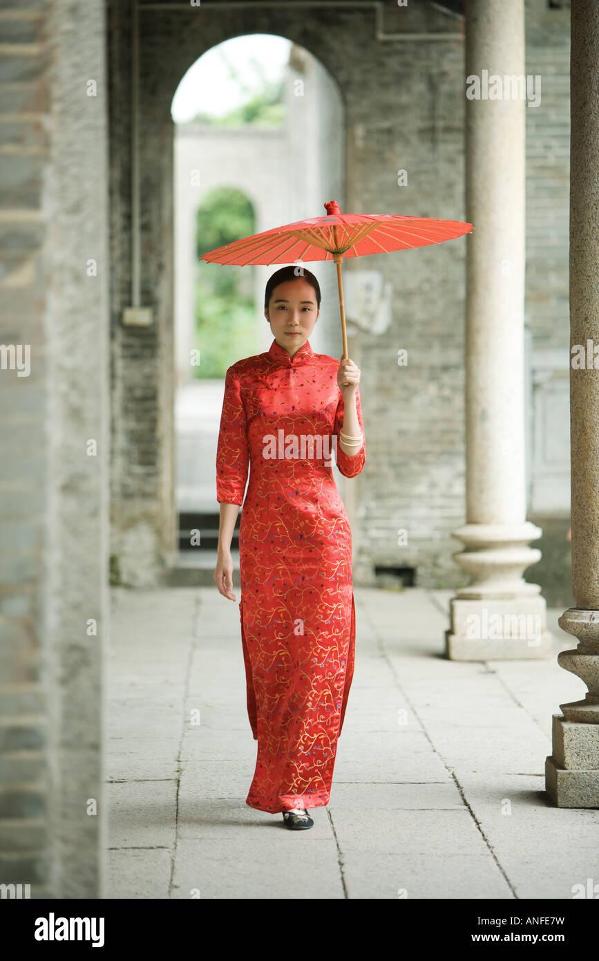 Junge Frau trägt traditionellen chinesischen Kleidung, zu Fuß mit Sonnenschirm Stockbild