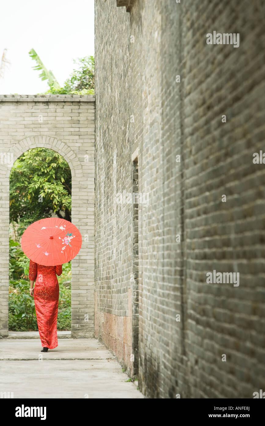 Junge Frau trägt traditionellen chinesischen Kleidung, zu Fuß mit Sonnenschirm, Rückansicht Stockbild