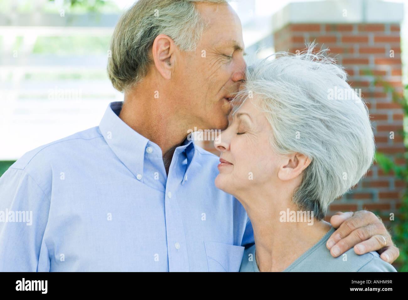 Reifer Mann küsst Frau Stirn, Seitenansicht Stockbild