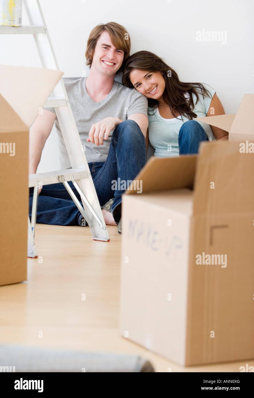 Paar sitzt neben Umzugskartons Stockbild