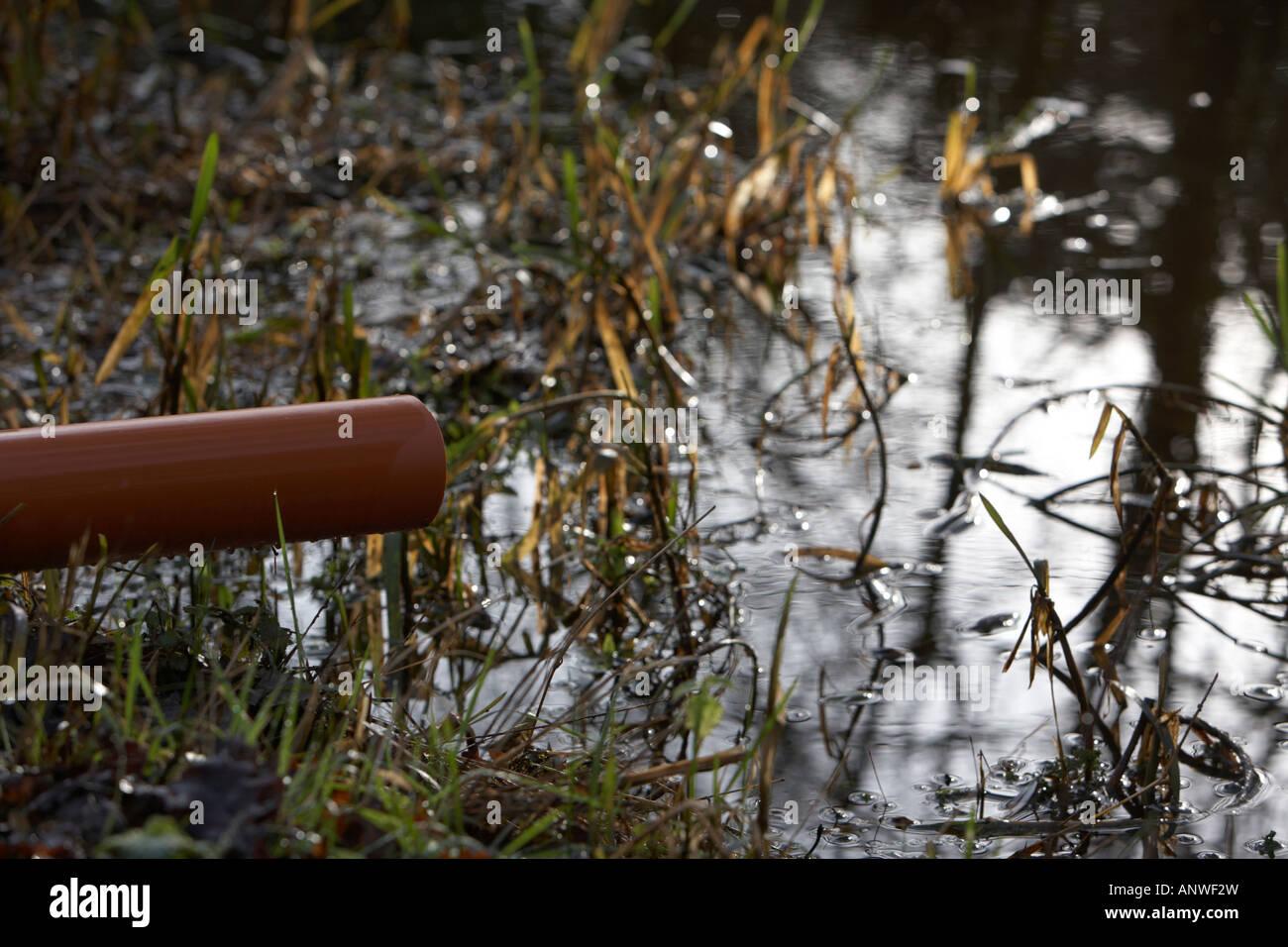 Kunststoff-Wasser Überlaufrohr in Fluss herausragen Stockbild