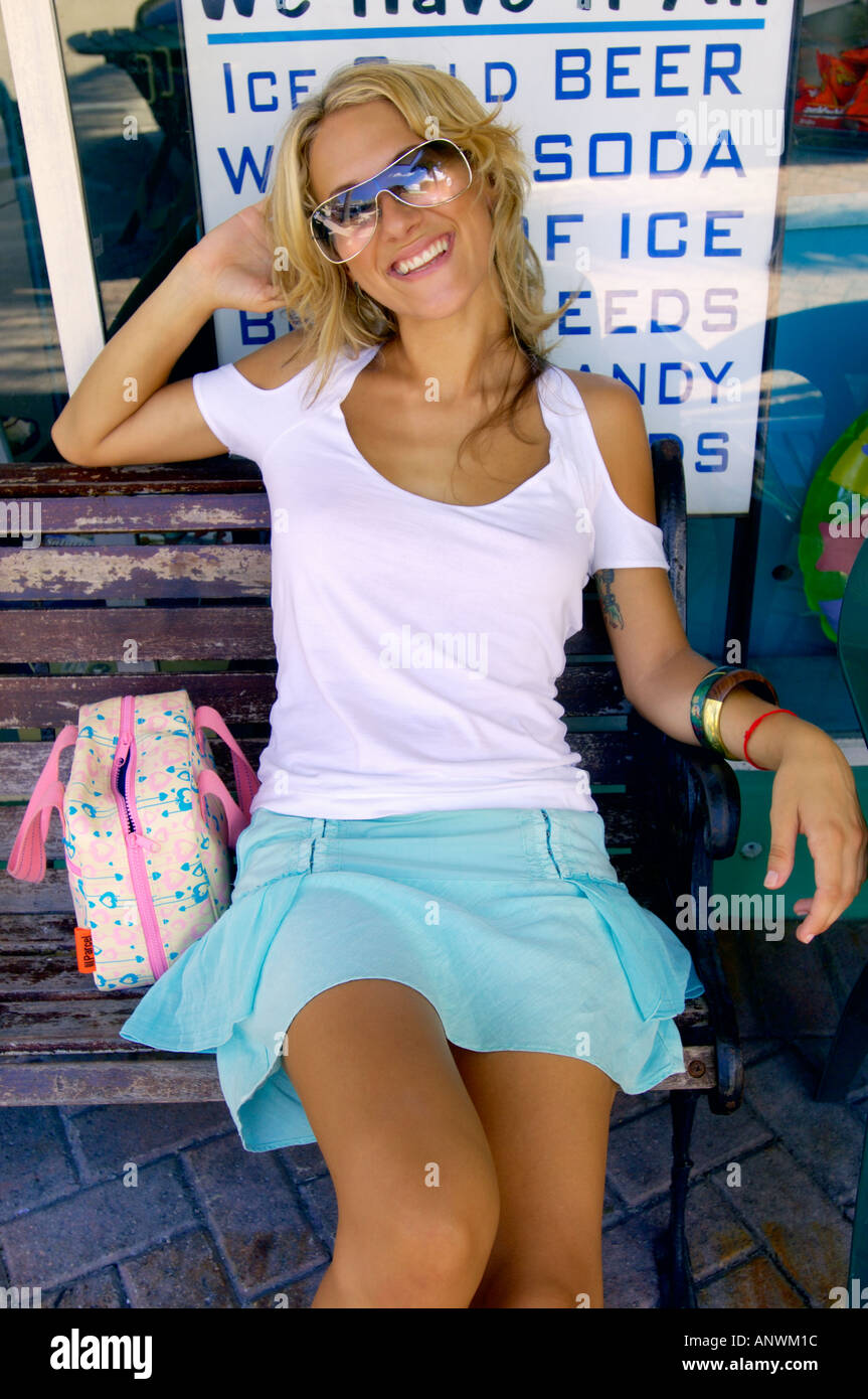Junge Frau sitzt auf Bank am Convenience-Store im Urlaub entspannen. Stockbild