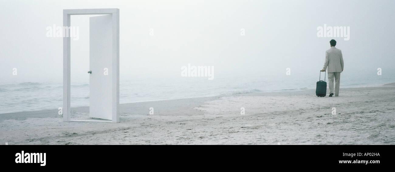 Mann mit Koffer zu Fuß am Strand in mittlerer Distanz, Türrahmen im Vordergrund Stockbild